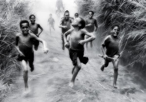 Village Boys chase a passing truck. Papua New Guinea. 1972 by Peter Bowater